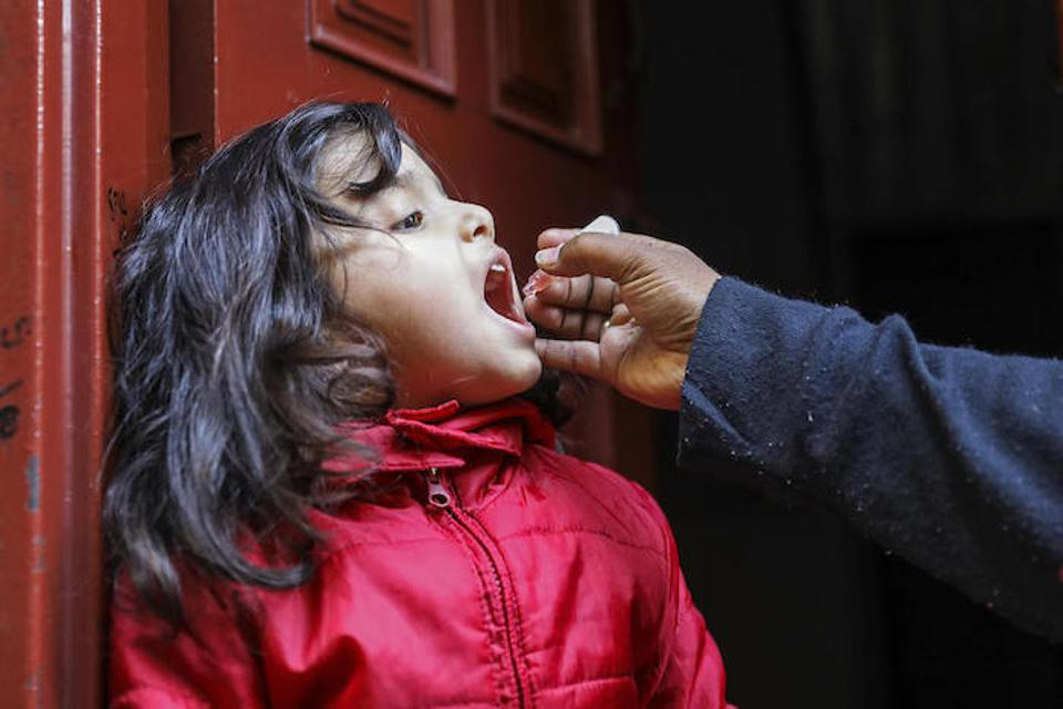 Four-year-old Aneesa is vaccinated by UNICEF-supported polio worker Saima Shahid in the doorway of her home in the Bhatti Gate area of Lahore Punjab Province, Pakistan.