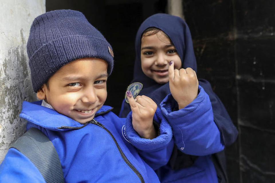 Five-year-olds Abdullah (left) and Mariyam proudly show the ink marks that signify they've been vaccinated against polio in the Ponch House area of Lahore Punjab Province, Pakistan.