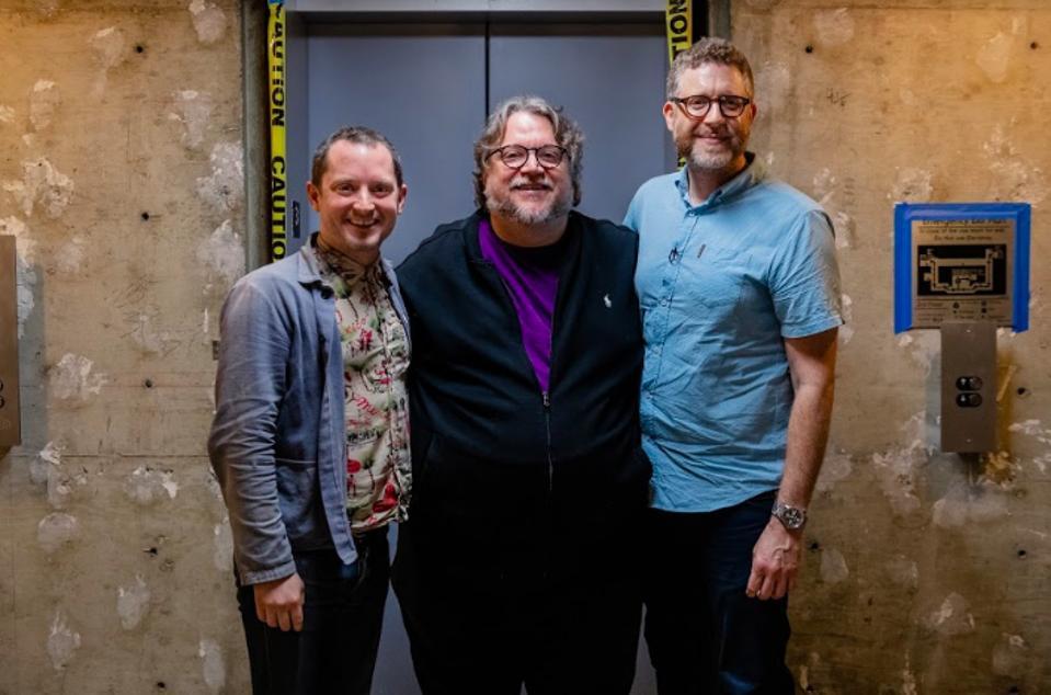 Elijah Wood and Daniel Noah meeting Guillermo del Toro in a hotel lobby