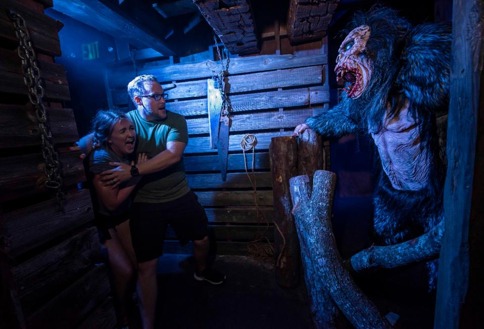 Costumed characters leap out at guests in the intricately-detailed haunted houses