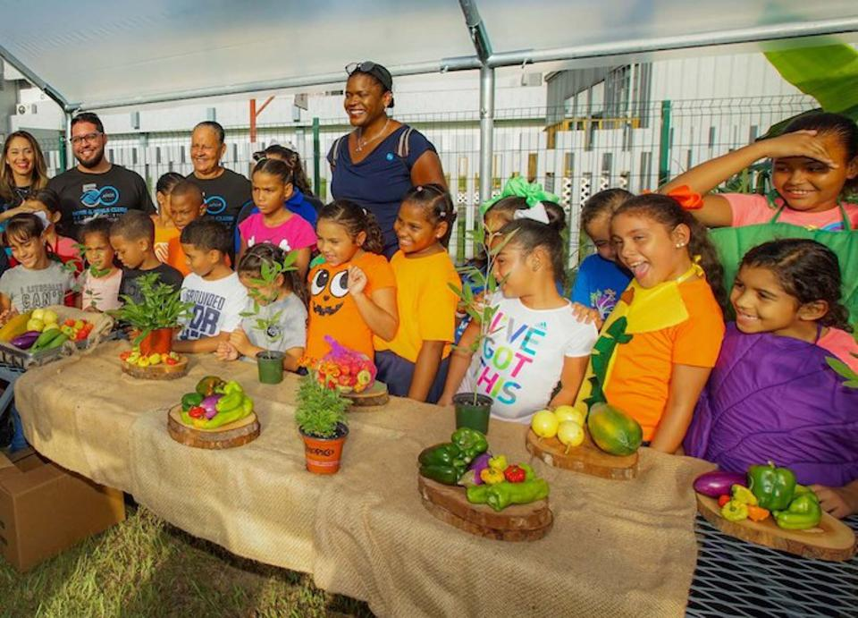 Children celebrate healthy eating and gardening at the Boys & Girls Clubs of Puerto Rico with UNICEF USA Chief Engagement, Advocacy and Global Programs Officer Anucha Browne (center) and BGCPR staff members.