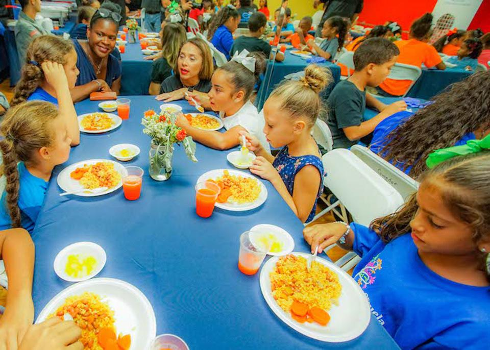 Anucha Brown, Chief Engagement, Advocacy and Global Programs Officer at UNICEF USA (top left) and Olga Ramos, President of the Boys & Girls Clubs of Puerto Rico, talk with kids enjoying a healthy dinner at the Las Margaritas Club.