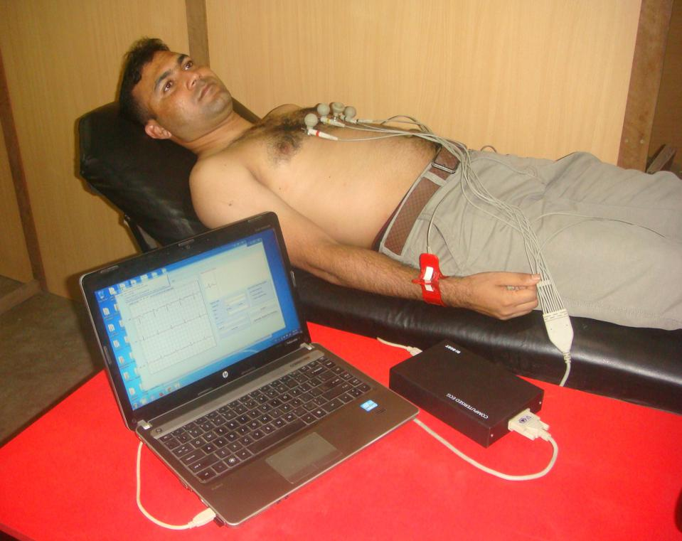 Shirtless man on bed, with cables connecting from his chest to a computer and black box