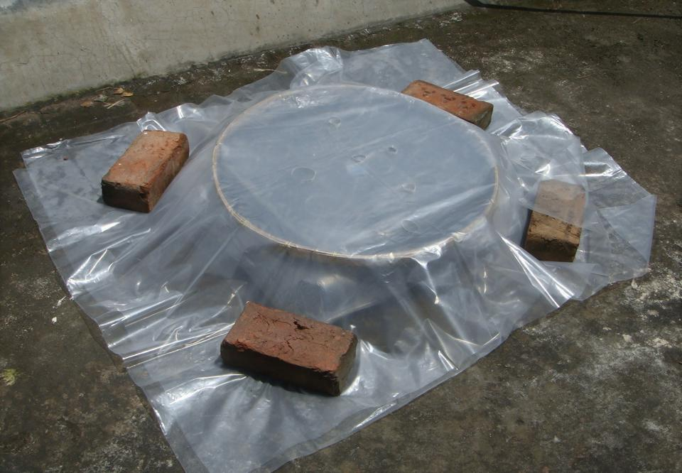 Plastic sheets above a round device, all weighted down with bricks