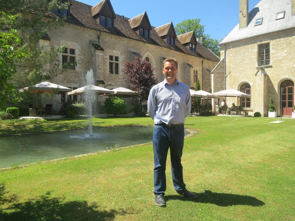 Englishman Clive Cummings standing in front of his Burgundy luxury hotel Abbaye de la Bussière
