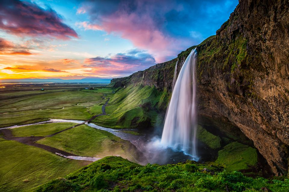 Travelers visit Iceland to see Seljalandsfoss.