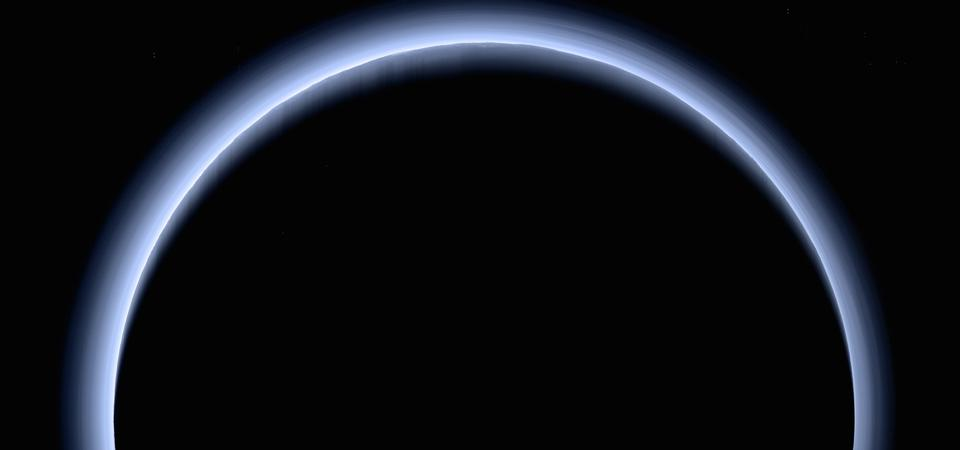 A near-true-color image taken by New Horizons after its flyby. Numerous layers of blue haze float in Pluto's atmosphere. Along and near the limb, mountains and their shadows are visible.