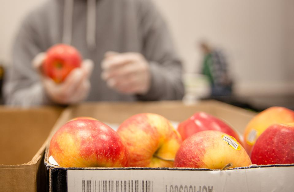 Box of apples with person in background packing the box