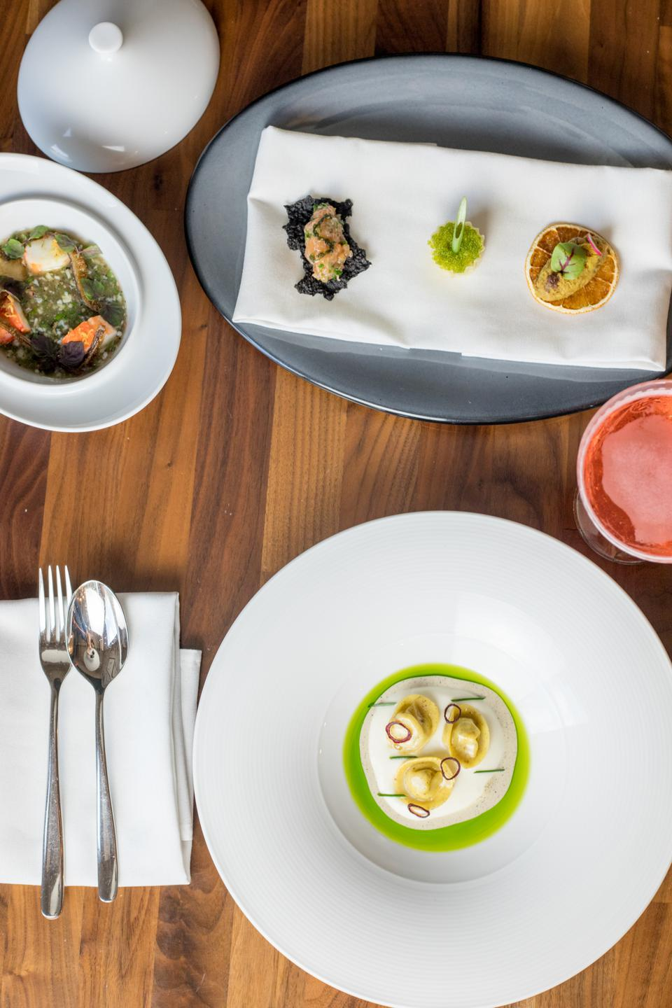 Three different dishes situated on a wooden table.