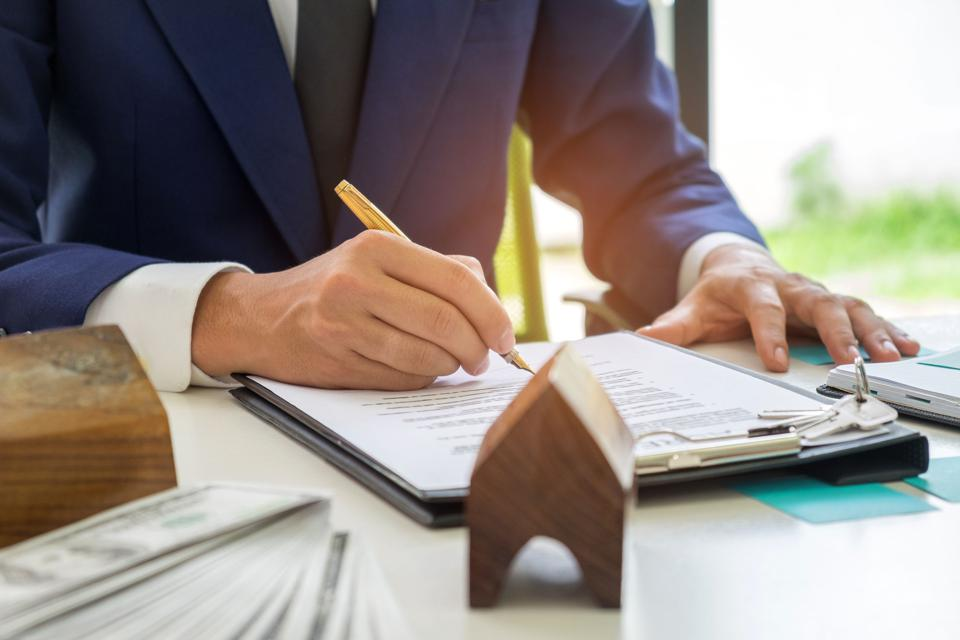 Estate agent signing contract on a house purchase agreement.