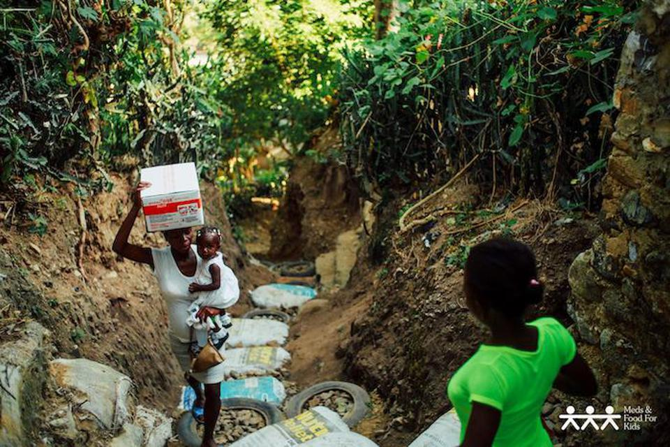 A mother carries her child and a carton of Ready-to-Use Therapeutic Food (RUTF) in Haiti. According to Wolff, RUTF tastes like the inside of Reese's Pieces candy.