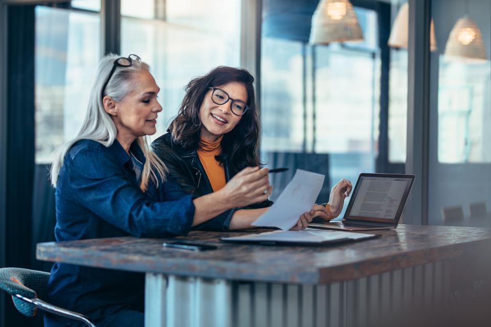 Two women analyzing documents at office