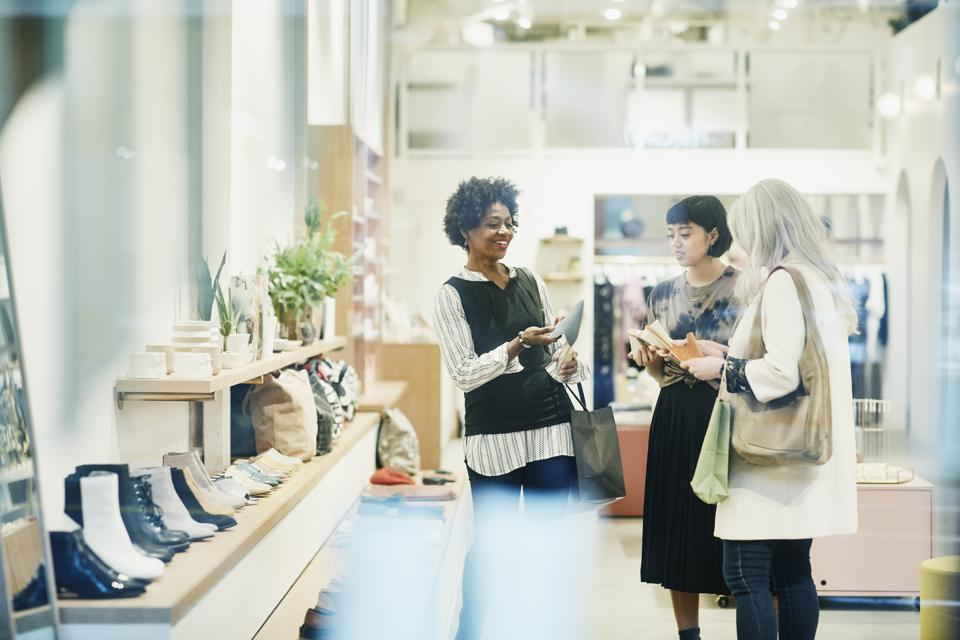 Smiling mature woman in discussion with store owner while shopping for shoes with friend