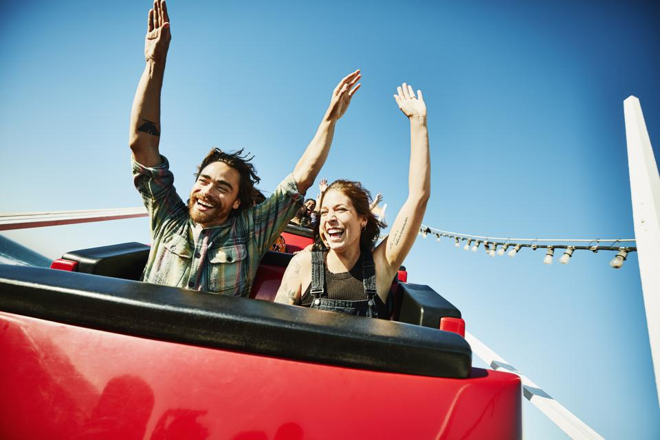 Laughing couple with arms raised riding roller coaster