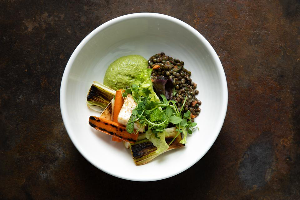 A white dish containing a plant-based meal of roast vegetables, lentils and purée