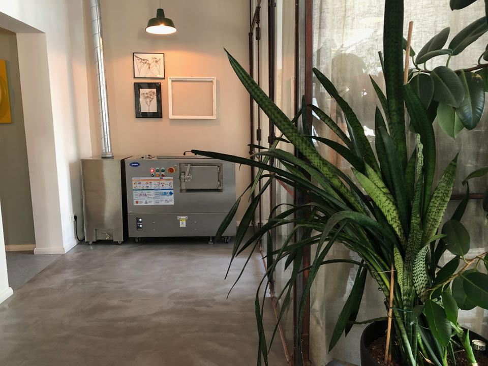 A photo of a corridor with a plant on the right hand side and a composting machine at the end up against the wall