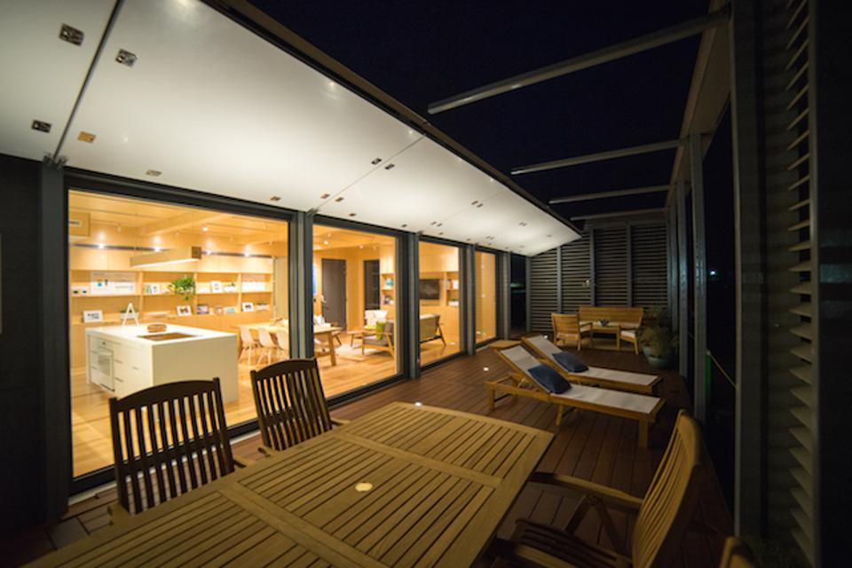 The operable shutters are secured open above the deck on the south side of the house.