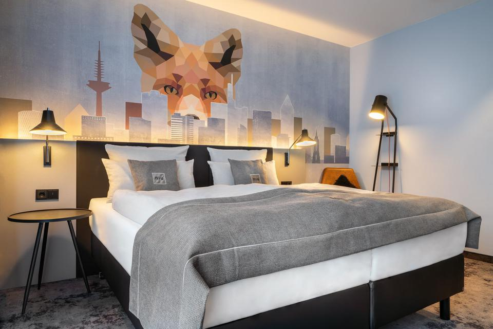 Cozy room with mural at Niu Charly Hotel in Frankfurt