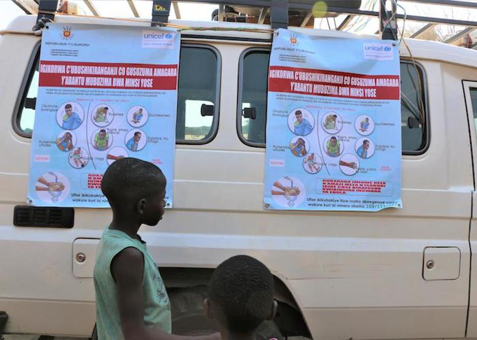 In Gatumba, Burundi in August 2019, a boy examines posters as part of an Ebola awareness campaign organized by UNICEF Burundi's Communication for Development (C4D) team.