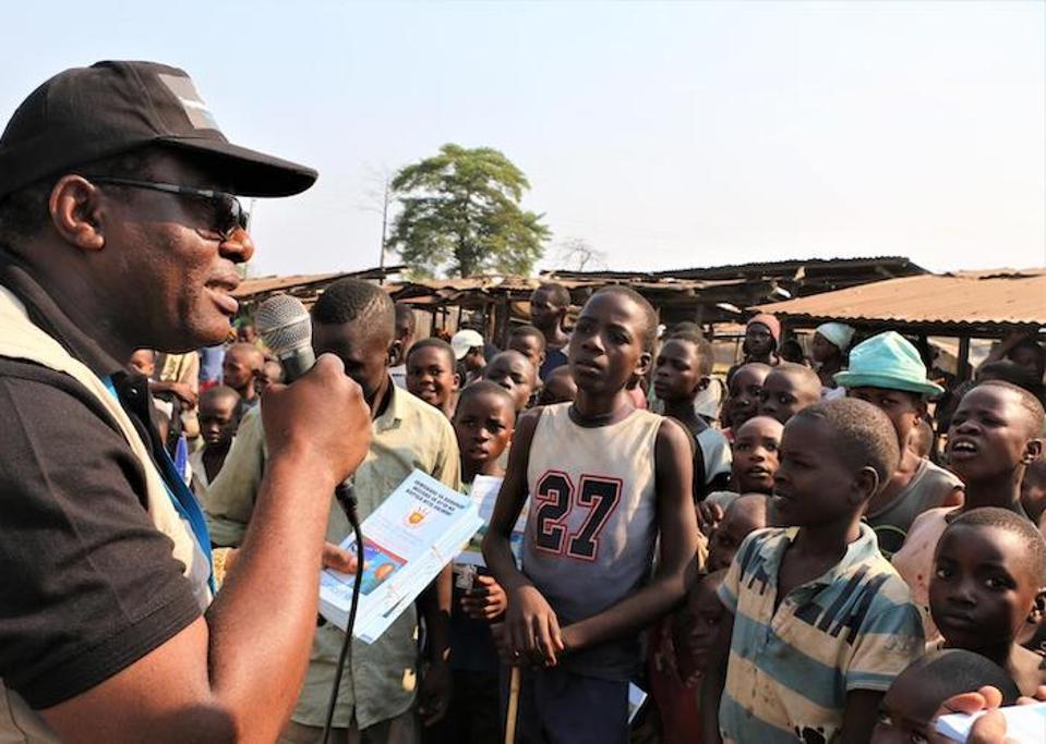 On August 7, 2019, Jean Louison Miango Makunda, UNICEF Burundi's Communication for Development (C4D) consultant on Ebola preparedness, speaks with children and distributes brochures in Gatumba, Burundi.