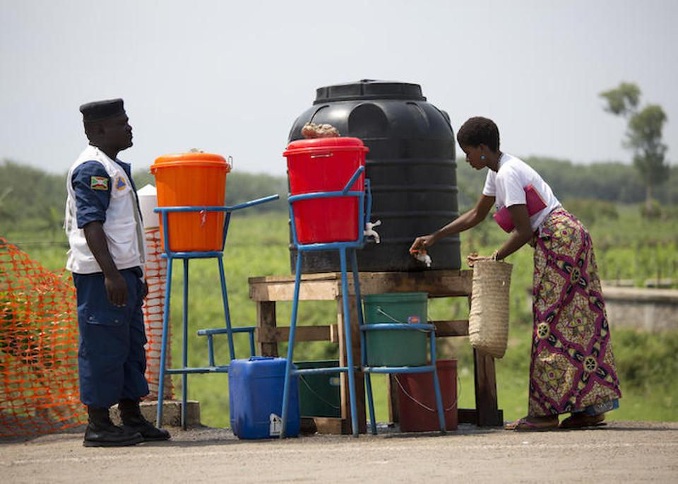On September 16, 2019, a woman washes her hands in chlorinated water at a border crossing from the Democratic Republic of the Congo into Burundi.