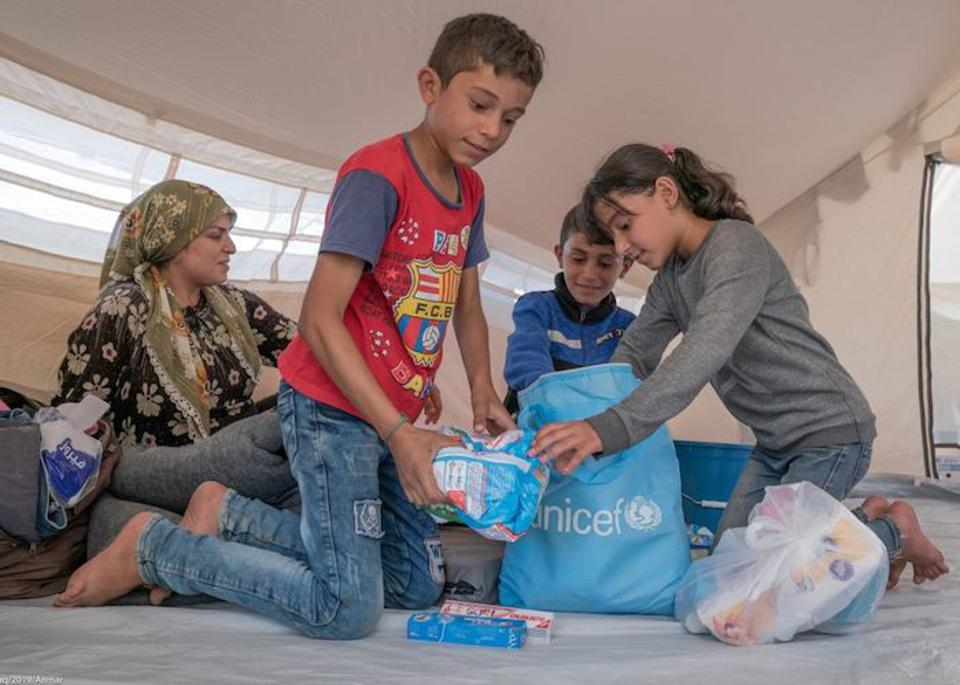 In Iraq, 7-year-old Majeed (in red shirt), 5-year-old Hesar (in blue shirt) and 8-year-old Divin, all from Hasakeh, Syria, open emergency kits distributed by UNICEF and partners.