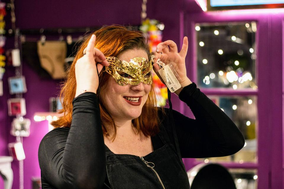 A woman tries on a gold mask at an event at Sh! sex store in London, UK