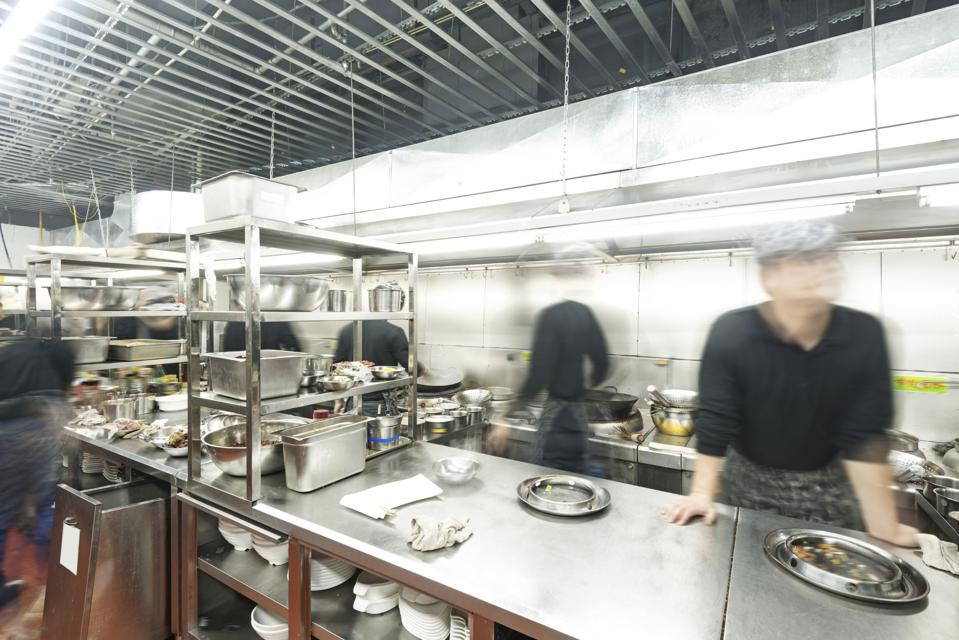 A photo of chefs working in a restaurant kitchen whose images a blurred to indicate they are in motion.