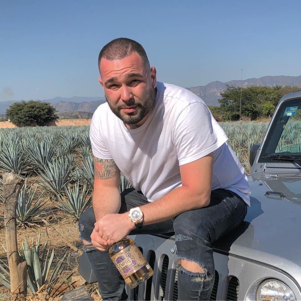 Alex Lacroix holding up a bottle of his tequila in front of the agave fields.