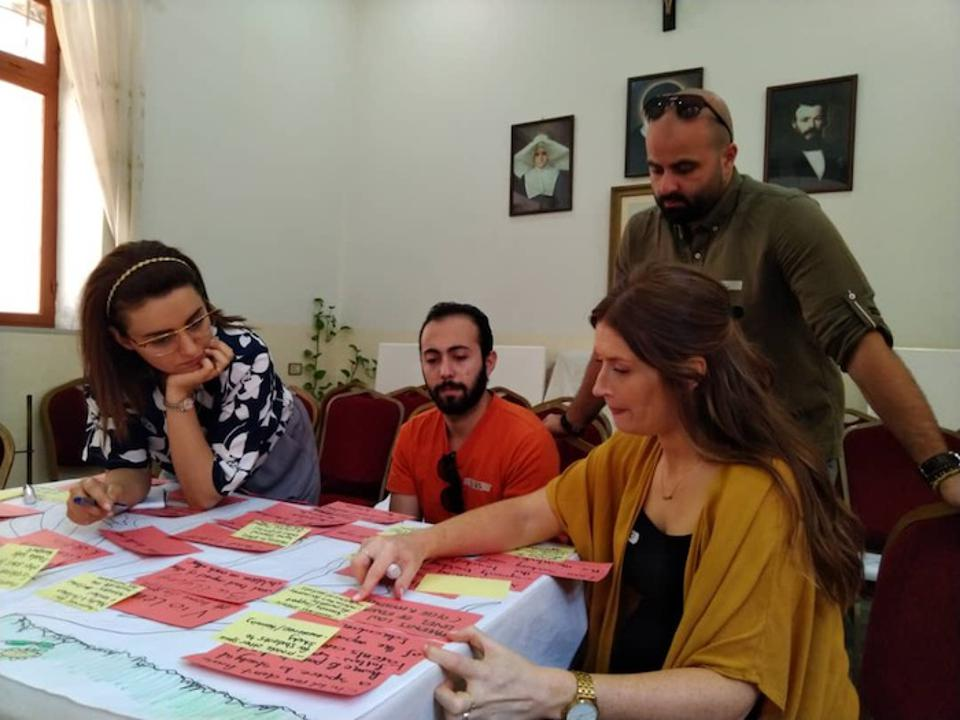 Rotary Peace Fellow Lucienne Heyworth (right, foreground) prepares and reviews curricula with colleagues. Heyworth views education as a basic human right that is often overlooked in conflicts.