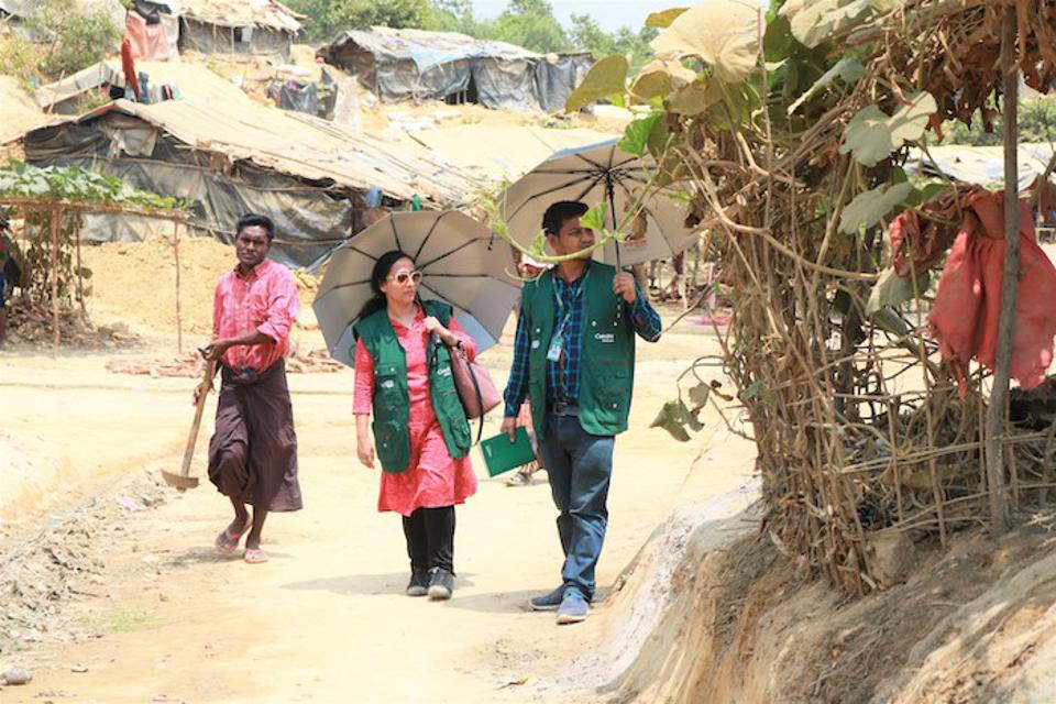 Hasina Rahman, center, walks through a refugee camp in Cox's Bazar, Bangladesh. Her work there focuses on lifesaving preventive care and nutrition services for children and pregnant women.