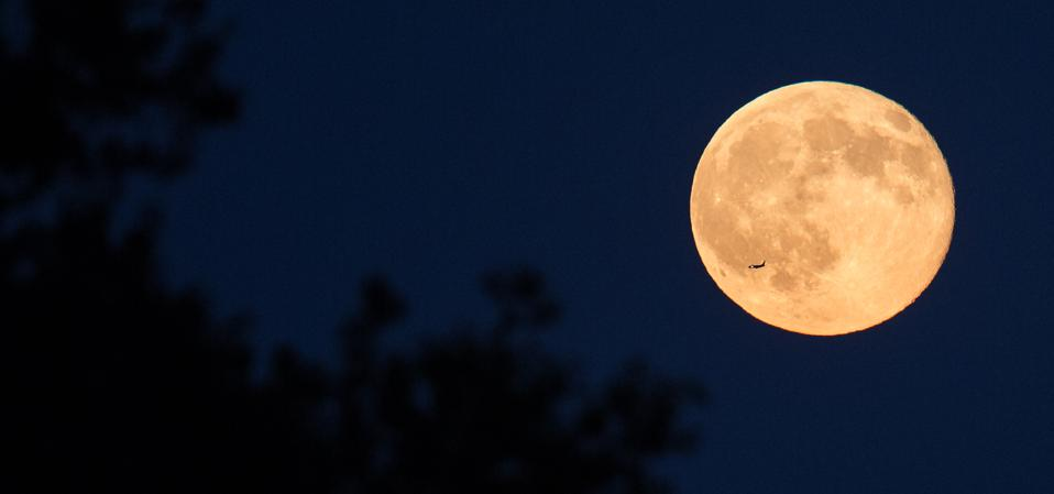 A plane is seen flying in front of a full moon.