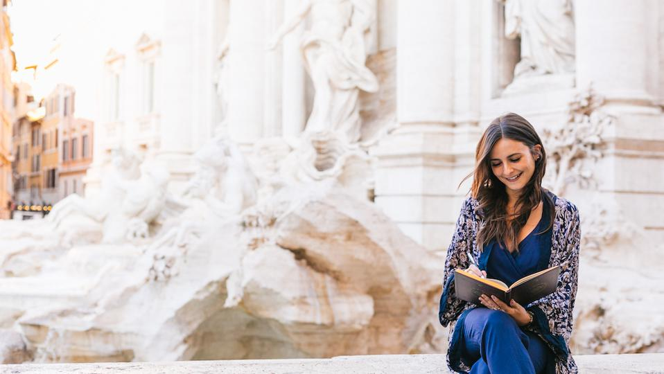 Entrepreneur woman sitting in Rome, reading a book and creating her brand story.