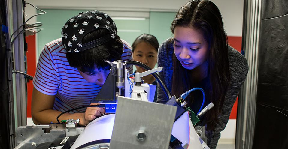 Three students work on an engineering project