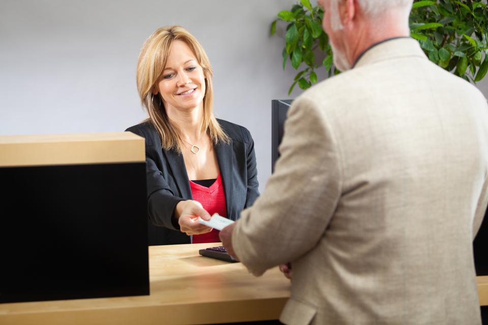 Bank Teller Working with Customer at Retail Bank