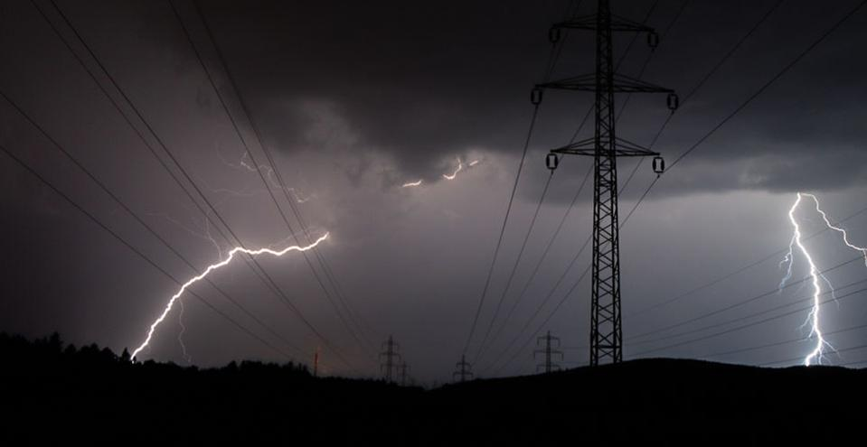 Dark image of high power transmission lines with lightning in the background