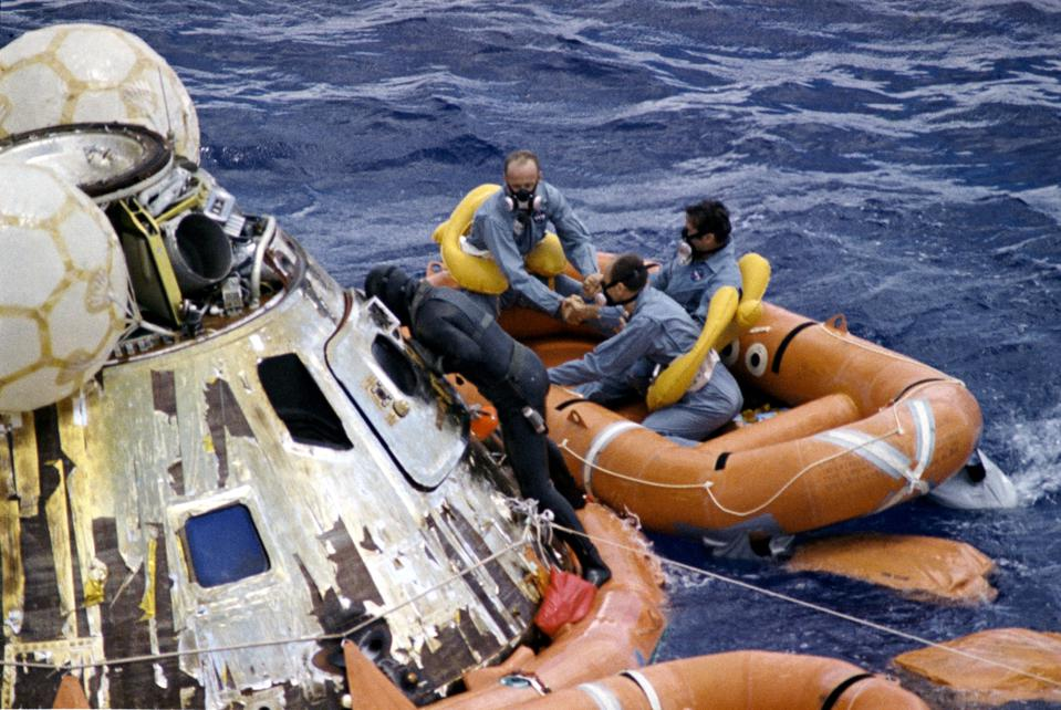 A United States Navy Underwater Demolition Team swimmer assists the Apollo 12 crew during recovery operations in the Pacific Ocean.
