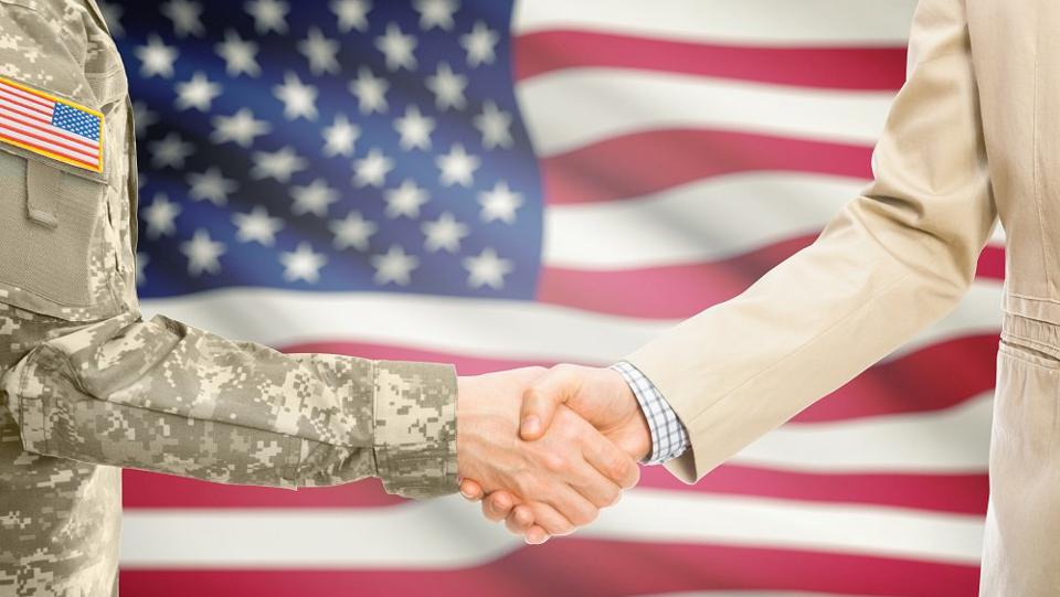 USA military man and civilian man shaking hands