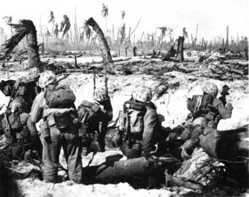 Marines near the beach on Namur island, await the word to attack Japanese troops concealed amidst palm trees shattered by an earlier naval bombardment.