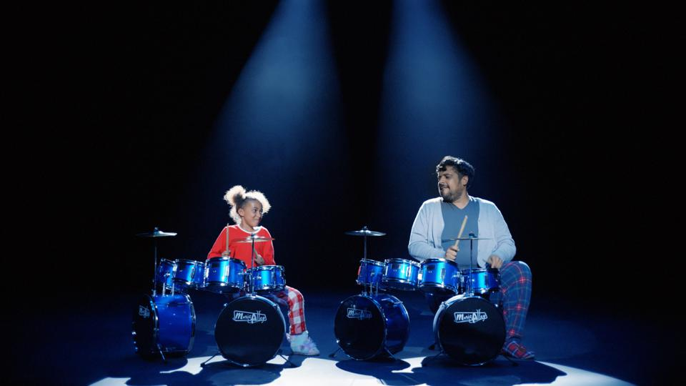 Argos father and daughter playing drums under spotlights.
