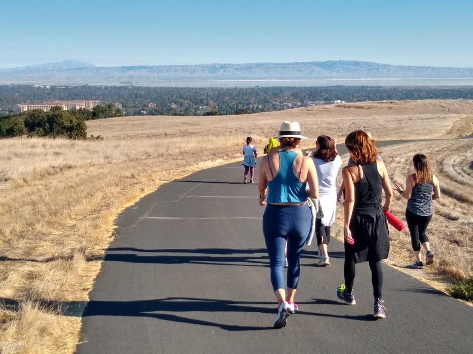 A group of women hikes the Dish on Stanford campus in the morning.