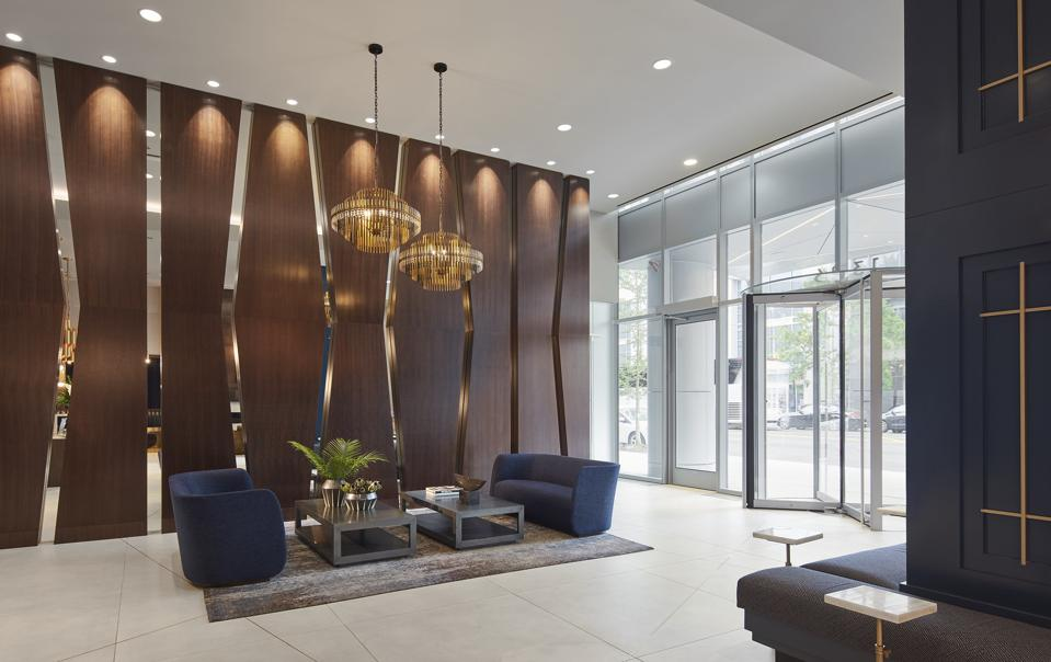 A wall of deep mahogany wood with mirrored cut-outs flanks the lobby interior, reminiscent of the glass angles on the building's exterior.