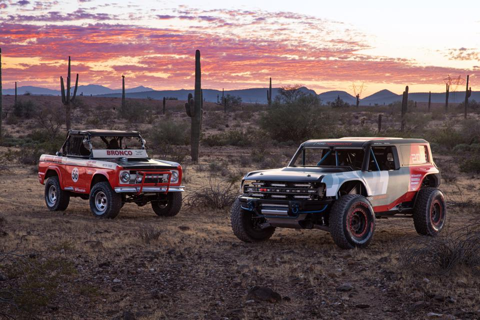 The vintage Ford Bronco sits next to the 2019 Bronco R Baja race truck it inspired.