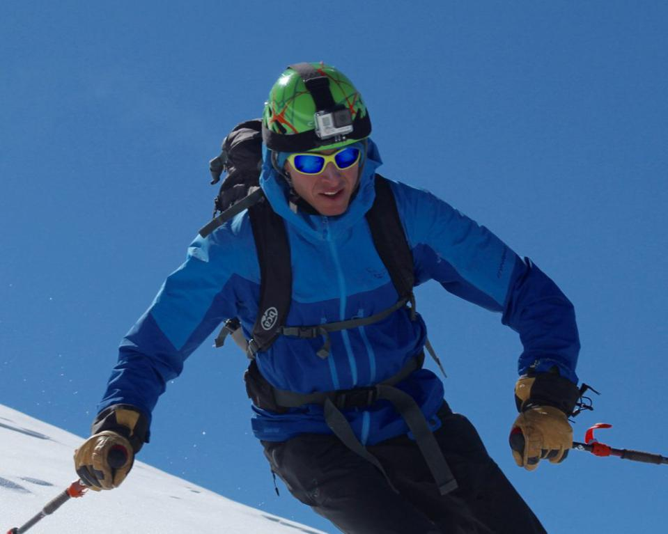 A skier wearing sunglasses swooshes down the slope.