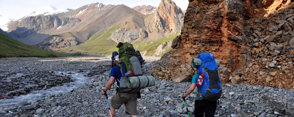Two backpakers hiking through the Alaskan wilderness.