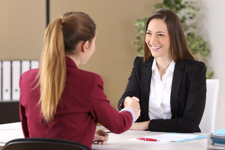 Two businesswomen handshaking at office