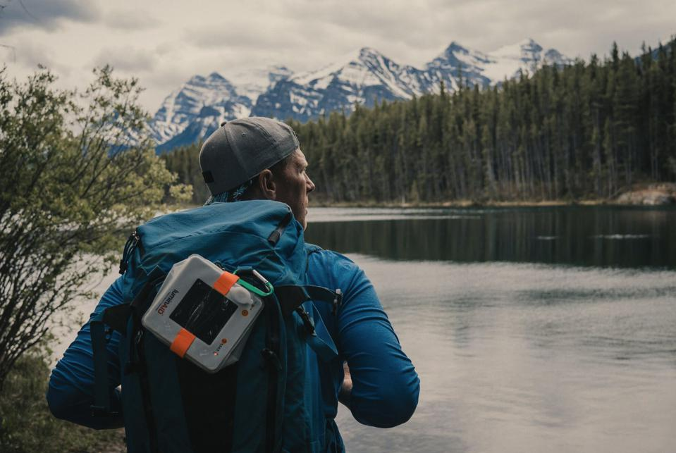 A hiker with the PackLite Max 2-in-1 Charger