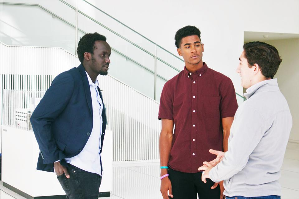 Three young men standing and talking.