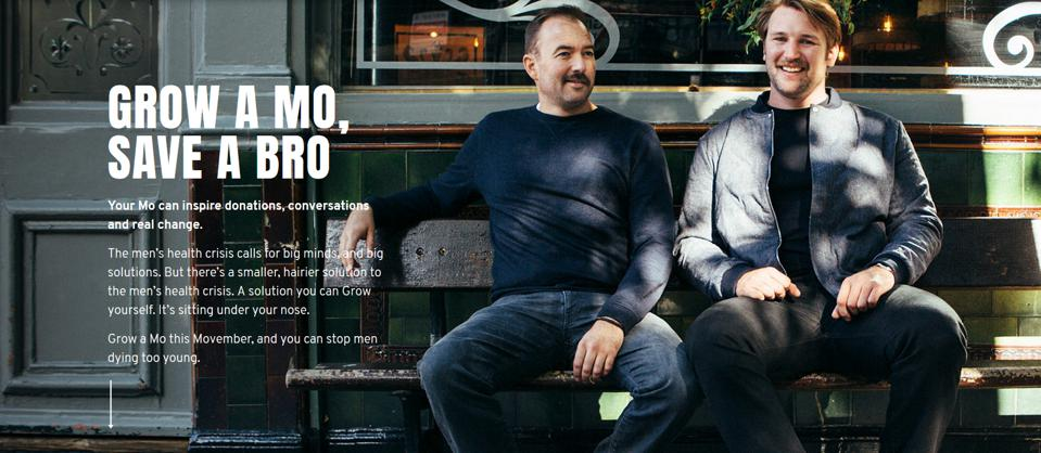Two men sitting on a bench and a text caption saying, ″Grow a Mo, Save a Bro.″