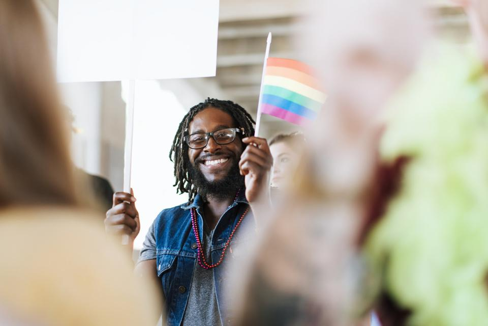 A black man smiles amidst a crowd holding a rainbow flag.